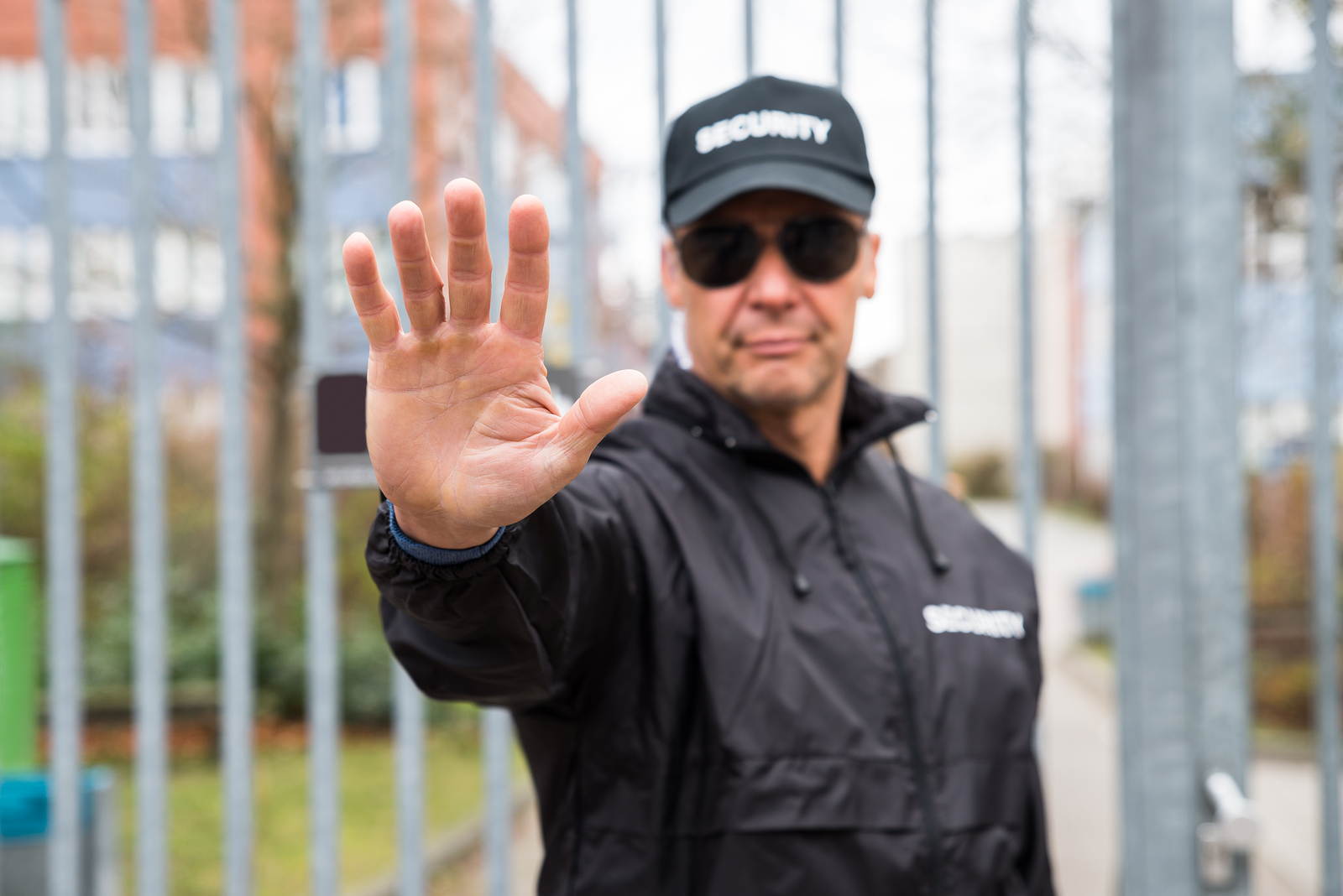 Confident security guard making stop gesture in front of gate